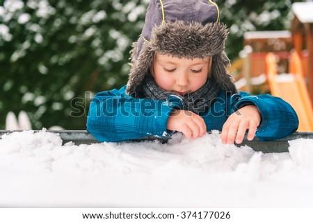 Adorable kid boy playing in sandbox full of snow, wearing warm hat  - stock photo