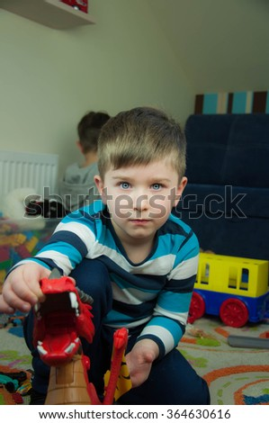Adorable kid boy playing with cars and toys at home