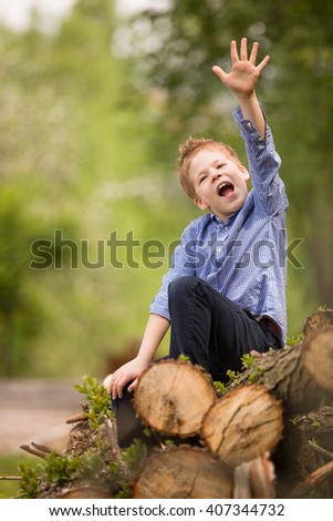 Adorable kid boy sitting on the pile of old trees and having fun. outdoors, countryside. Happy child in nature, sitting in a pile of trunks. - stock photo