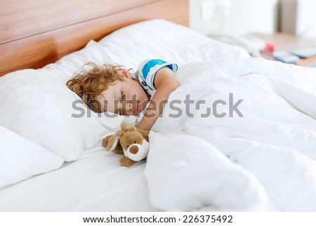 Adorable kid boy sleeping and dreaming in his white bed with toy. - stock photo