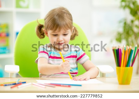 adorable kid child girl drawing with colorful pencils - stock photo