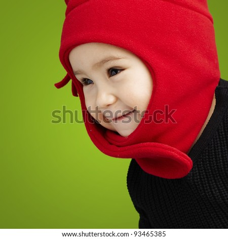 adorable kid face wearing winter clothes over green background - stock photo