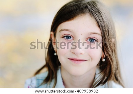Adorable kid gir with long brunette hair playing in the sun in summer park - stock photo