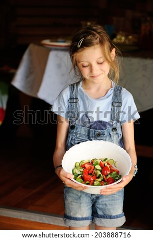 Adorable kid girl holding a bowl with homemade green salad with olive oil - stock photo
