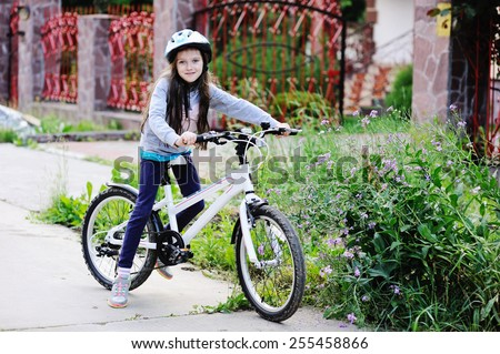 Adorable kid girl in blue helmet going to ride her bike