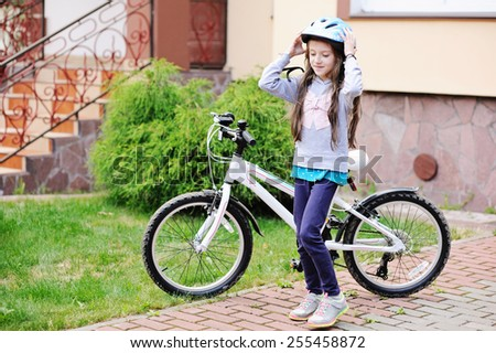 Adorable kid girl in blue helmet going to ride her bike  - stock photo