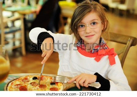 Adorable kid girl in sweater and glasses eating pizza in italian restaurant - stock photo