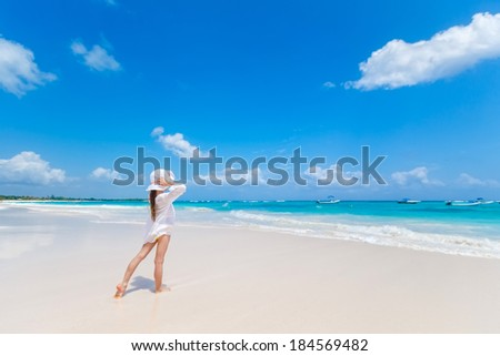 Adorable kid girl in white dress and hat staying ob beach and looking at Caribbean sea - stock photo