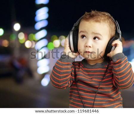 adorable kid wearing headphones and looking up, outdoor - stock photo