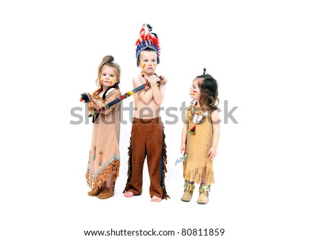 Adorable kids dress up for Halloween in indian costumes.  They are ready for war with their weapons and fierce expressions. - stock photo