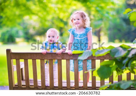 Adorable kids, little curly girl and a cute baby boy, brother and sister, sitting together on a wooden bench in a garden, hugging and kissing, relaxing and having fun on a sunny summer day - stock photo