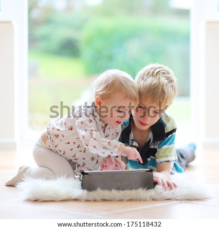 Adorable kids, teenager boy with toddler sister playing on tablet pc laying indoors on the tiles floor - stock photo