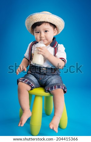 Adorable korean baby boy drinking milk from bottle on blue background - stock photo