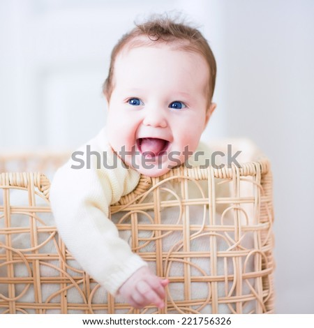 Adorable laughing baby sitting in a laundry basket - stock photo