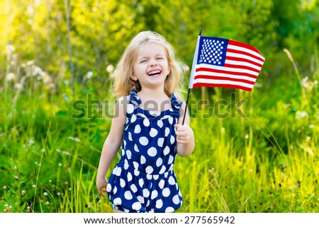 Adorable laughing little girl with long curly blond hair holding american flag and waving it on sunny day in summer park. Independence Day, Flag Day concept