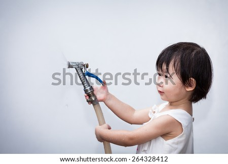Adorable little asian (thai) girl play with water hose on wall white background - stock photo