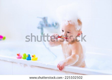 Adorable little baby boy brushing his teeth, taking bath playing with foam and colorful rubber duck toys in a sunny white bathroom - stock photo
