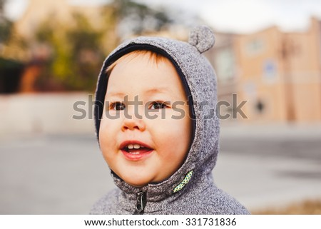 Adorable little baby boy excitedly looking at sunset paining his face with warm tones. Infant boy with unusual asian appearance in bear suit smiles while having blond hair and asian eyes. Mixed race - stock photo
