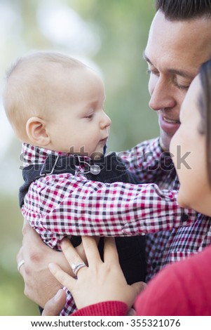 Adorable Little Baby Boy Having Fun With Mother and Father Outdoors. - stock photo