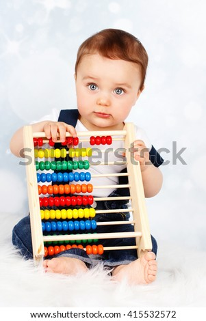 Adorable little baby boy holding abacus - stock photo