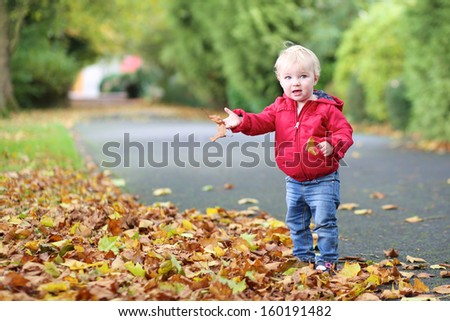 Adorable little baby girl in bright red coat plays with yellow leaves in autumn park on a warm sunny day