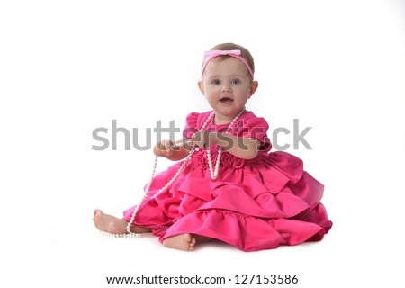 Adorable little baby girl  in  pink dress sitting on floor - stock photo