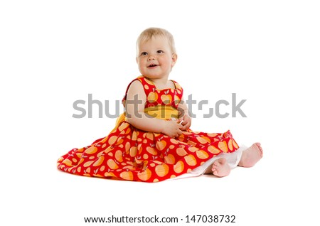 Adorable little baby girl in red dress sitting on floor isolated on white background