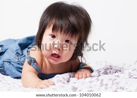 Adorable little baby girl laughing, creeping & playing in the studio, isolated on towel