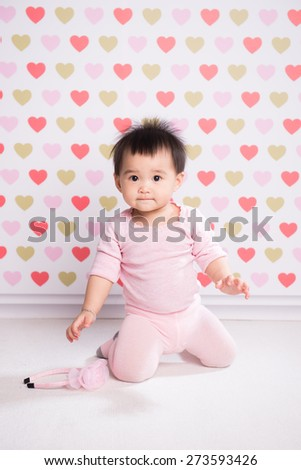 Adorable little baby girl smiling, sitting on the floor, studio shot, isolated on white background, lovely baby portrait.  - stock photo