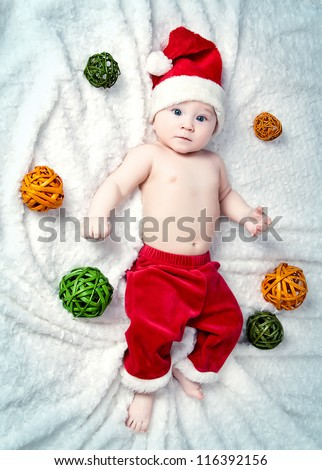 Adorable little baby Santa Claus with Christmas balls - stock photo