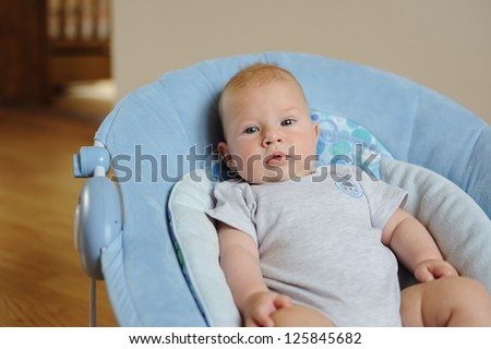 Adorable little baby sitting in a blue chair and looking in camera