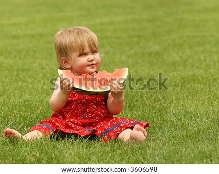 adorable little baby sitting on the grass with a piece of watermelon - stock photo