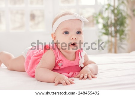 Adorable little baby with blue eyes on bed - stock photo