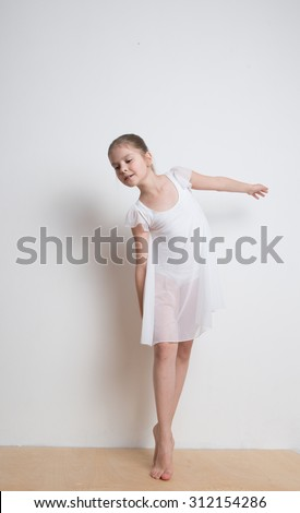 Adorable little ballerina in a white dress