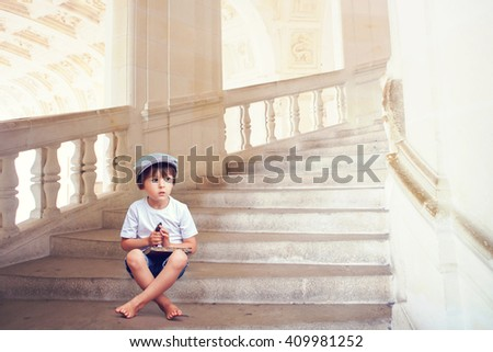 Adorable little barefoot boy, sitting on a beautiful staircase with book and a big key, thinking, summertime - stock photo