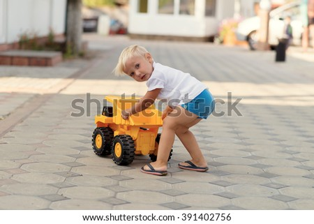 Adorable little blond boy playing with big yellow car outdoors. - stock photo