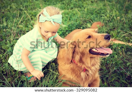 Adorable little blond girl playing with her cute pet dog - stock photo