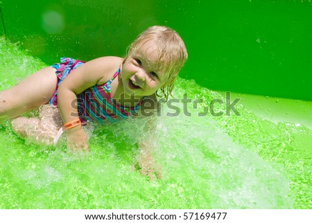Adorable little blond girl smiling on a green waterslide - stock photo