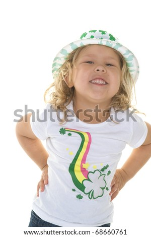 Adorable little blond girl smiling wearing St. Patrick's Day shirt and hat in the studio - stock photo