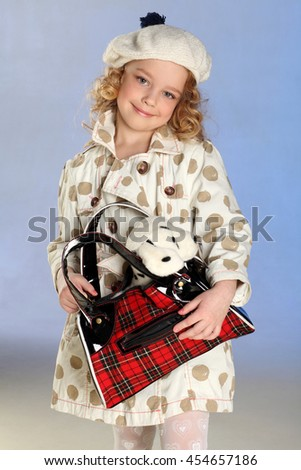 Adorable little blond girl standing and holds handbag with a plush toy. Beautiful child with curly hair playing with toy puppy. - stock photo