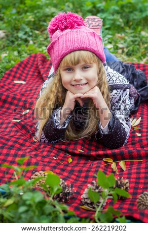 Adorable little blond girl with long blond hair in autumn park. Beautiful little young baby in a pink hat. Beautiful child lies on a red plaid.  - stock photo