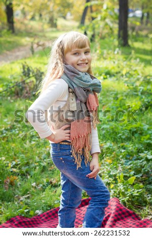 Adorable little blond girl with long blond hair in autumn park. Beautiful little young baby stands in a scarf.  Lovely child smiling  - stock photo