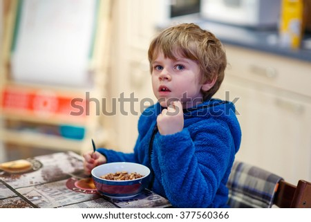 Adorable little blond kid boy eating cereals for breakfast or lunch. Healthy eating for children. At nursery or at home. - stock photo