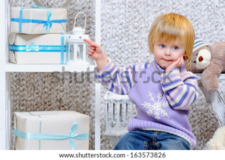 Adorable little blond toddler wearing lilac sweater with snowflake and pointing shy at gift boxes - stock photo