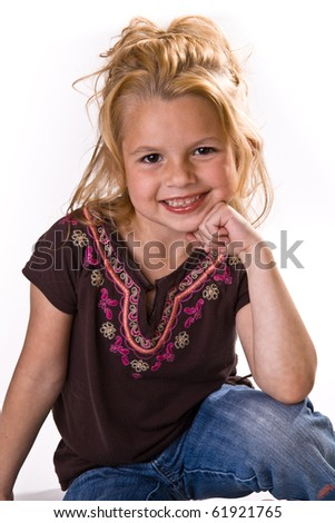 Adorable little blond wearing jeans with her chin on her hand.