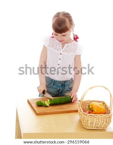 Adorable little blonde girl cut with a knife cucumber standing at the table - isolated on white background - stock photo