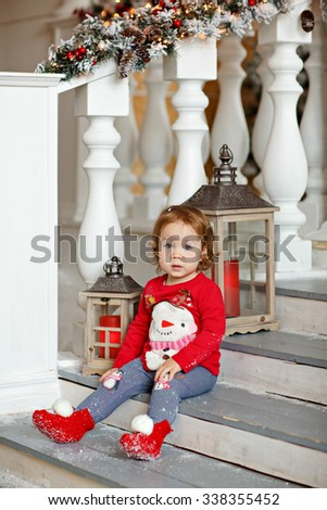 Adorable little blonde girl little girl in a sweater with a snowman sitting on the stairs in Christmas decorations near the lanterns and candles - stock photo