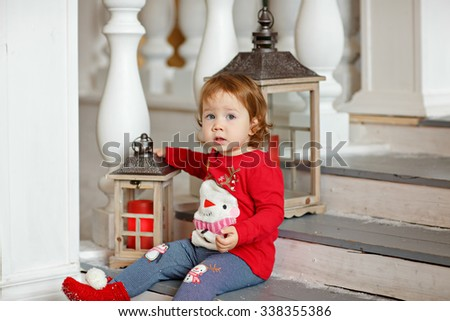 Adorable little blonde girl little girl in a sweater with a snowman sitting on the stairs in the Christmas decorations next to the lanterns - stock photo