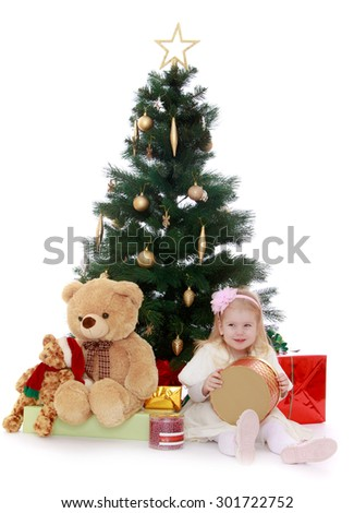 adorable little blonde girl sits on the floor near the Christmas tree. Girl holding a round box which is a gift. Beside her sits a large Teddy bear and other gifts. The girl is preparing to celebrate - stock photo