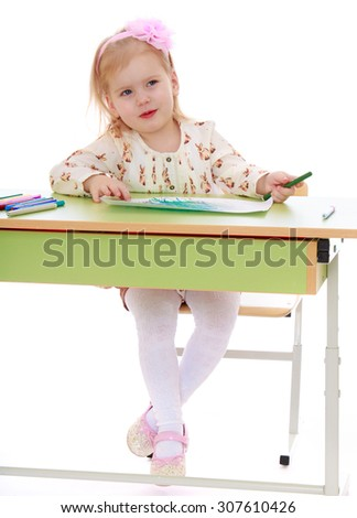 Adorable little blonde girl with gray eyes draws markers sitting at the Desk-Isolated on white background - stock photo